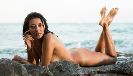 Portrait of  young sexy  nude girl lying  on stones at  ocean shore