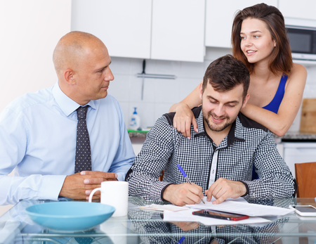 Smiling young couple signing financial agreement with social worker at home