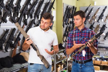 Two young men choosing pneumatic weapon in military shop