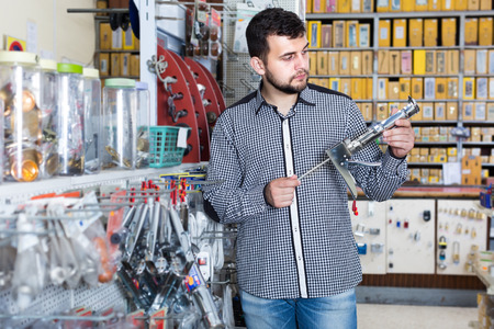 Young male deciding on best glue gun in houseware store