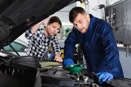 Young female master with foreman are replacing an oil in the car in workshop