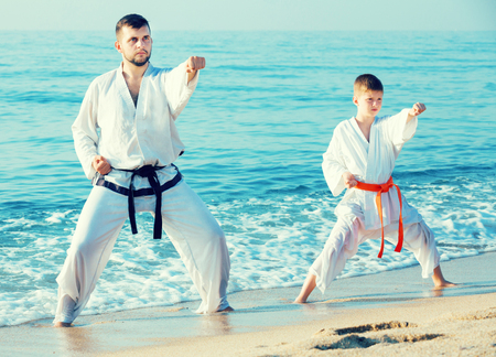 Man and boy doing karate poses at sunset sea shore