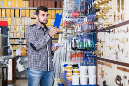 serious man customer examining various glue tubes in houseware store