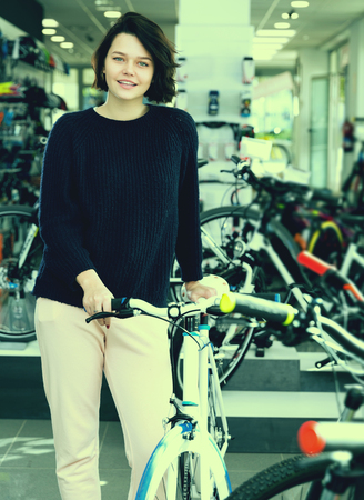 smiling female standing with bicycle in the store Standard-Bild