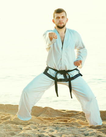 young man practicing karate positions at ocean quay in sunset Stockfoto