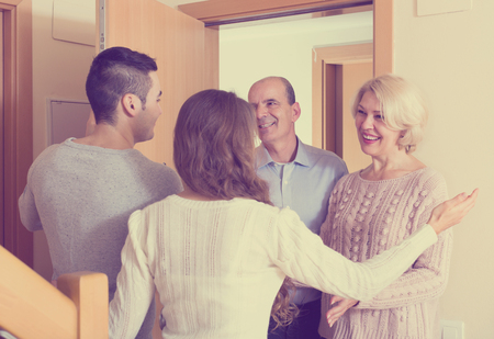 junge Familie, die ältere Eltern einlädt, hereinzukommen