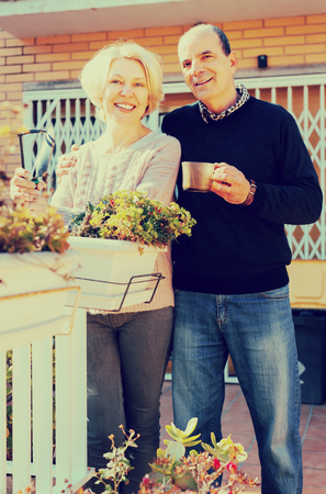 Smiling retired couple outdoors outside their home in a patio. Husband hugs hus wife and holds a cup of coffee Stockfoto