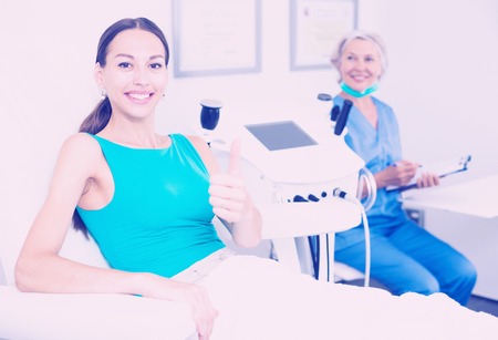 Smiling female patient satisfied after cosmetological procedure in esthetic clinic Stock Photo