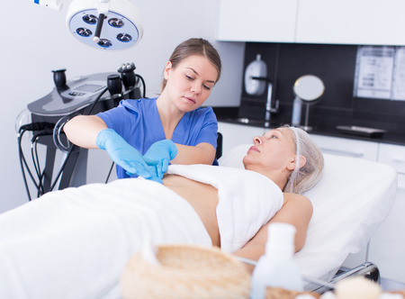 Young cosmetologist examining mature female body before procedure in esthetic clinic