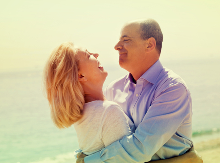 Eldelry tourist couple at sea beach on vacation smiling together