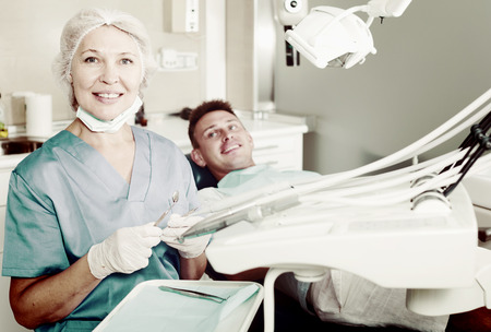 Female dentist with male patient in modern dentistry