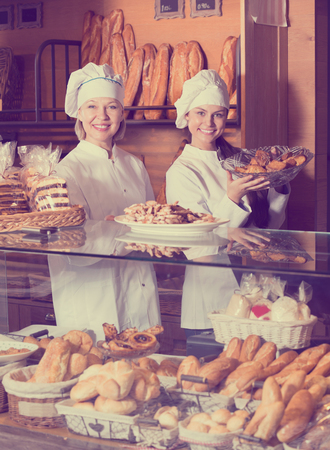Bakery commerce staff offering bread and different pastry for sale 免版税图像 - 107091084