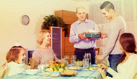 Happy people congratulating heartily family member at home