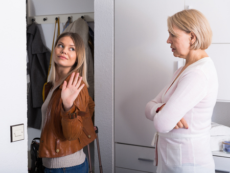 The elderly mother escorts her leaving adult daughter at home Stock Photo
