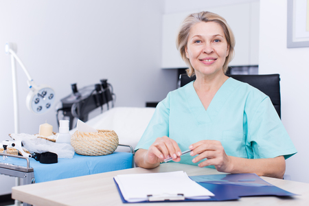 Qualified female beautician sitting at table in aesthetic clinic, recording client cards