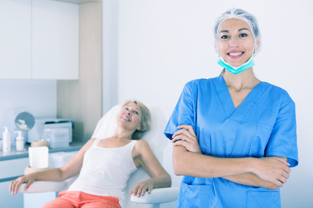 Female beautician standing in clinic of esthetic medicine with hands crossed