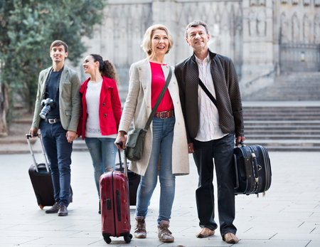 Two happy positive smiling couples with baggage sightseeing and smiling in spring Archivio Fotografico