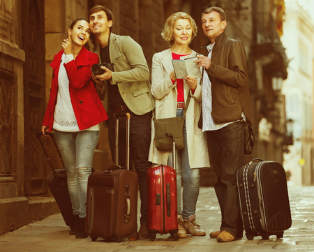 Portrait of  smiling spanish tourists with map and baggage seeing the sights in European city