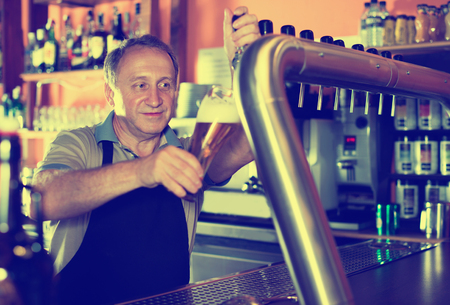 Smiling  cheerful positive  barman is pouring unbottled beer with foam for client in the bar. 版權商用圖片
