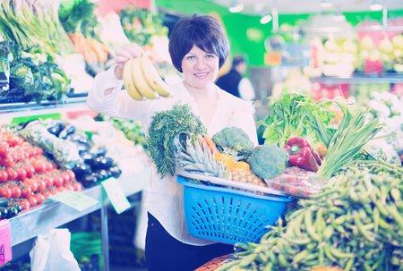 Adult female taking fruits and vegetables with basket on the store