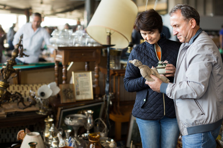 cheerful mature spouses buying retro handicrafts on indoor flea market Banque d'images