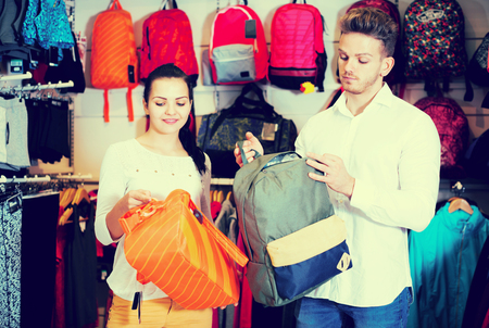 Young positive couple choosing new sports bag in sports store Reklamní fotografie