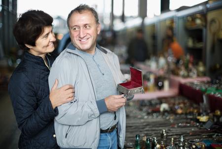 Loving senior family couple choosing vintage things at sale on market