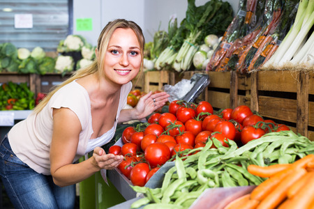 smiling young woman customer picking fresh ripe tomatoes in supermarket