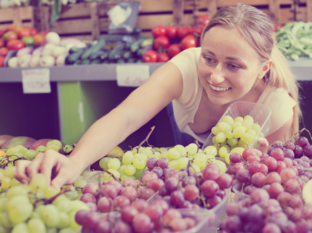Glad positive young woman customer buying sweet ripe grapes on marketplace