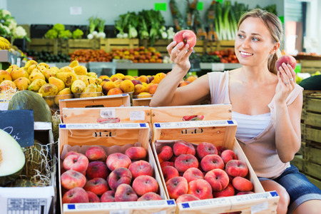 Glad young charming woman customer choosing peaches on fruit market Stok Fotoğraf