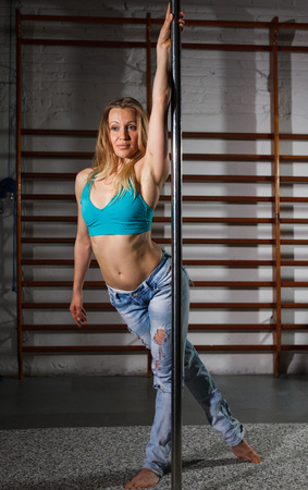 Sexy young woman in ripped jeans practicing pole dancing in dark fitness studio