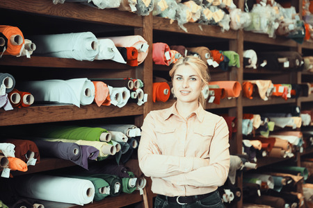 Successful female owner of fabric store standing near shelves with various cloth rolls