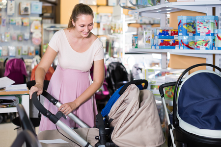 concentrated pregnant woman looking for baby carriage from assortment at kids shop