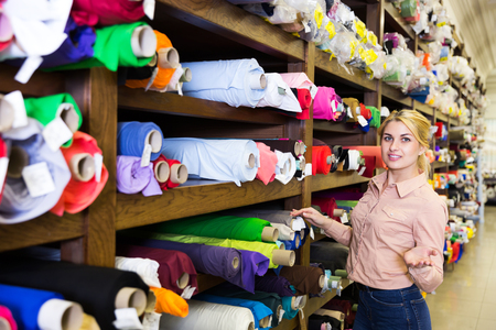 Portrait of blonde salesgirl working in fabric store, demonstrating wide range of stylish cloth Фото со стока