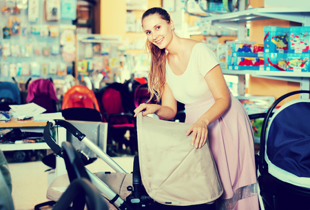 Happy glad  smiling pregnant woman buying baby stroller in kids mall
