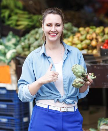 Portrait of positive woman who is choosing artichokes in the farmers market