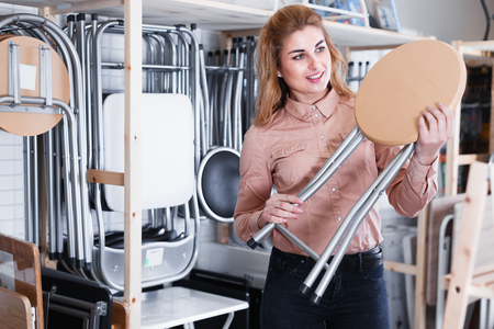 Glad woman looking for new stylish tabouret for apartment in furniture salon