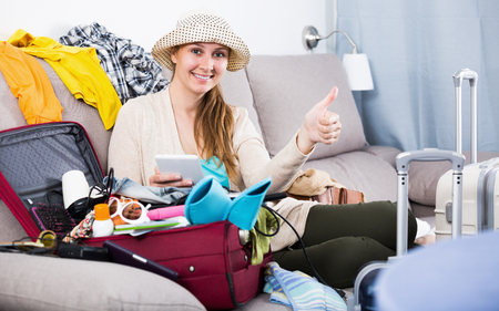 Smiling young woman preparing to depart for holiday at home