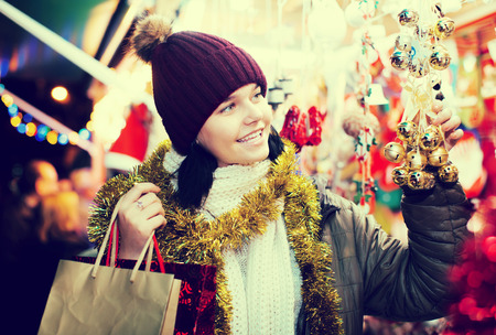 Cheerful teen  girl near the customer counter with Christmas gifts