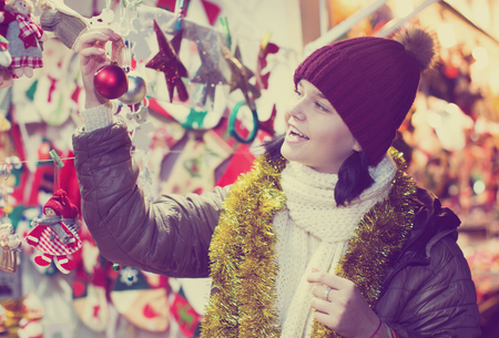 Smiling teen  girl near the customer counter with Christmas decoration Stock Photo