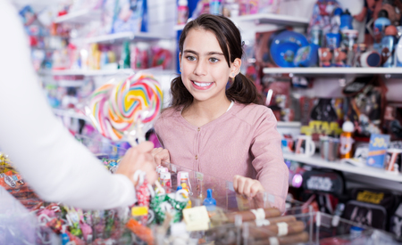 Smiling girl buying  sweet candies from seller in the candy store