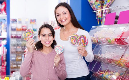 Smiling female and girl with colored lollipop in sweet-shop