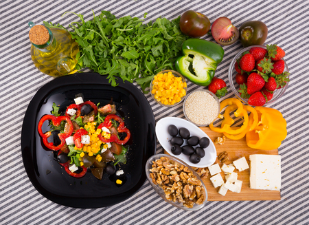 Image of ready-made salad and its ingredients on the table indoors.