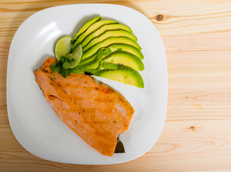 Photography of plate with fried trout fillet with avocado in restaurante. Banco de Imagens