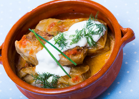 Close up of cabbage rolls in leaves of cabbage  in clay pot with sour cream