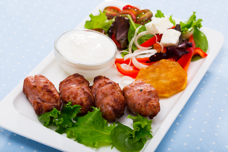 Dish of Bulgarian cuisine Kebapche - grilled meat sausages served with green salad and young cheese