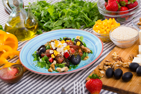 Plate with ready-made salad and its ingredients for recipe in restaurante.