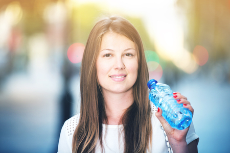 Young woman drinking water from bottle in hot weather outdoors
