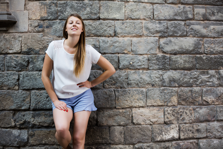 Portrait of smiling young woman on old stone cathedral wall background
