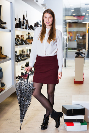 Cheerful woman is posing in modern shoes in shoes shop. Stock Photo